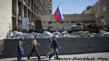 ARCHIV 2014 *** epa04217987 People pass under a Russian flag in front of the occupied administration building in Donetsk, Ukraine, 21 May 2014. The previous day, NATO said that it saw no evidence of Russian troops pulling back from the border with Ukraine, despite such an order by Russian President Vladimir Putin. EPA/ROMAN PILIPEY +++(c) dpa - Bildfunk+++ |
