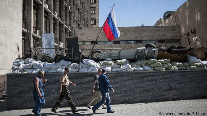 People pass under a Russian flag in front of the occupied administration building in Donetsk, Ukraine