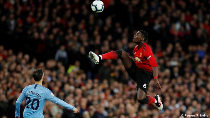 Paul Pogba leaps in the air during Manchester United - Manchester City match