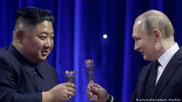 Russian President Vladimir Putin and North Korean leader Kim Jong Un clink glasses during a reception (picture-alliance/dpa/V. Sharifulin)