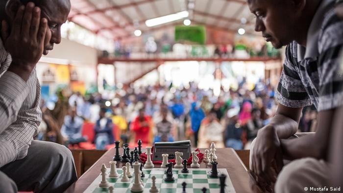 Check Mate, Everyday Africa: Zwei Schachspieler, über das Brett gebeugt, im Hintergrund Zuschauer (Mustafa Said)