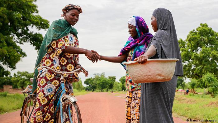 Shaking Hands, Everyday Africa: Drei Frauen, eine mit Fahrrad, die anderen zu Fuß, begrüßen sich auf einer Straße (Nana Kofi Acquah)
