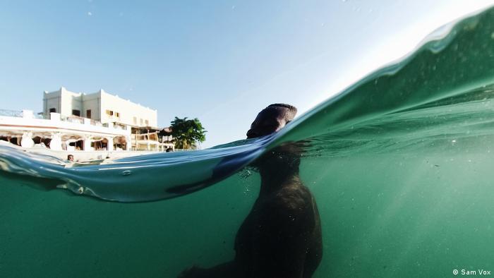 Foto: Floating in Water, Everyday Africa. Ein Mann im Wasser, Kameraperspektive halb im Wasser (Sam Vox)