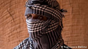 A man, his face wrapped in a turban to conceal his identity
