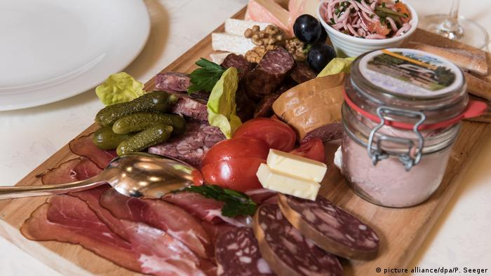 Lots of sliced meat on a wooden platter