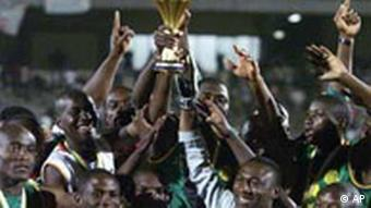 Members of Cameroon's team hold up the trophy after the Africa Cup of Nations