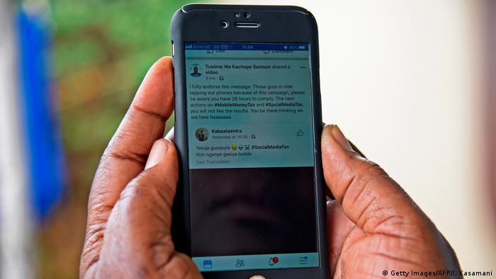 A woman reads a message on social media tax as she scrolls through her Facebook account on her phone in Kampala