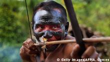 A Waiapi man aims bow and arrow at the Waiapi indigenous reserve in the Manilha village, in Amapa state, Brazil, on October 13, 2017. The Waiapi are one of the most traditional tribes in Brazils Amazon, but modern life is getting closer and the forest dwellers are learning how to navigate between two worlds. / AFP PHOTO / Apu Gomes (Photo credit should read APU GOMES/AFP/Getty Images)