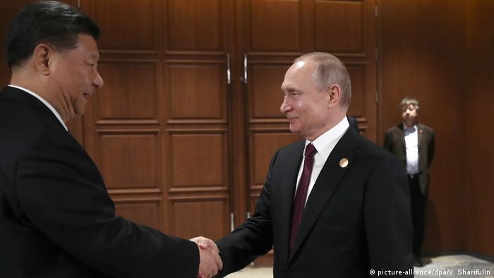 Xi Jinping shakes hands with Vladimir Putin