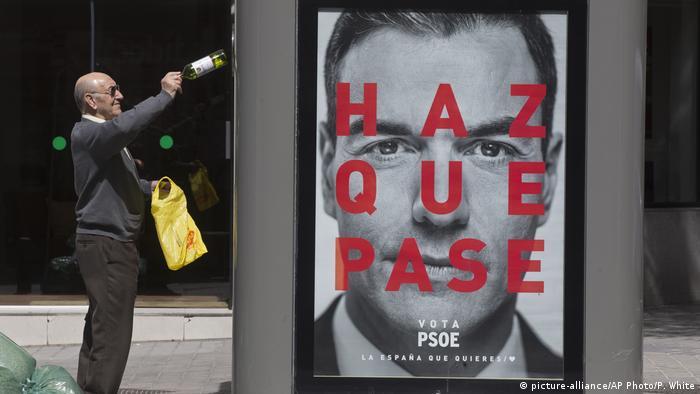 Homem deposita garrafa num contêiner de reciclagem com a foto do premiê espanhol Pedro Sánchez