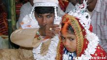 Malda, INDIA: An Indian groom puts vermilion, the holy mark belived the as sign of hindu marriage, on the forehead of his underage bride during a mass marriage programme in the village of Malda, some 360 Kms. northeast of Kolkata, 02 March 2006. India amended its Child Marriage Restraint Act in 1978, setting 18 as the minimum age for a woman to marry and 21 for a man, and lawmakers hoped in vain that the threat of fines and imprisonment would curb under-age marriages, but the practice continues. AFP PHOTO/STR (Photo credit should read STRDEL/AFP/Getty Images)