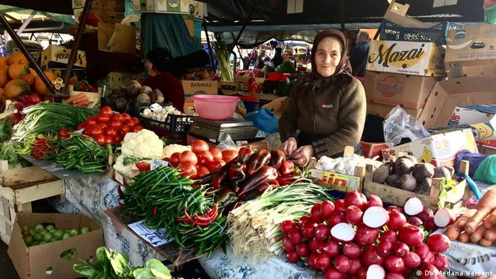A woman stands behind piles of fruits and vegetables at a market