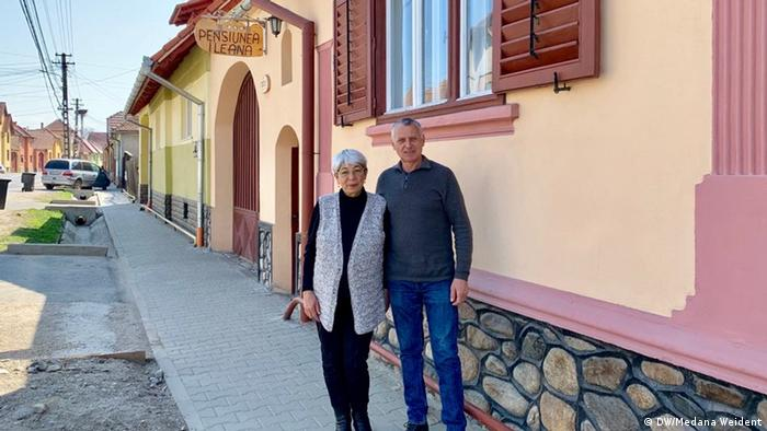 Dorin Beu and Ileana stand outside the guest house in Orlat that they run