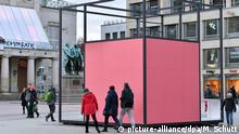 People walking around a pink cube which is the installation Gropius Room Pavilion