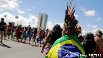 An individual dressed in a Brazilian flag and wearing a indigenous headdress protests in the street
