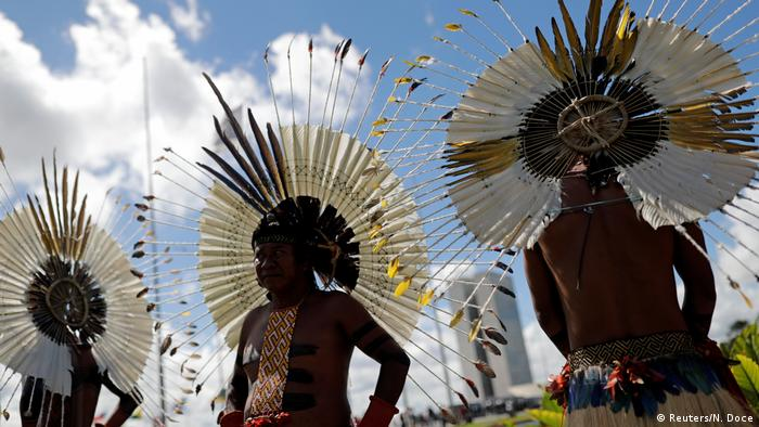 Three members of an indigenous group wearing headdresses