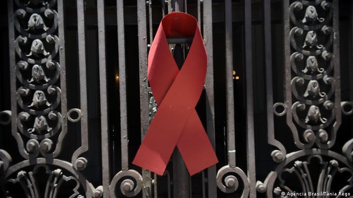Laço vermelho do combate à aids pregado em portão de ferro