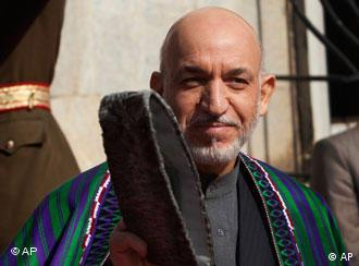 Afghan President Hamid Karzai gestures to journalists as he heads to receive U.N. Secretary-General Ban Ki-moon, unseen, at the presidential palace in Kabul, Afghanistan, Monday, Nov. 2, 2009. Afghanistan's election commission has canceled Saturday's presidential runoff and proclaimed Karzai victor of the war-ravaged nation's tumultuous ballot. (AP Photo/Ahmad Masood, Pool)