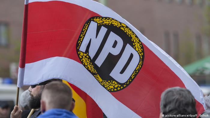 An NPD supporter waves an NPD flag at a demonstration in Berlin (picture-alliance/dpa/F. Schuh)