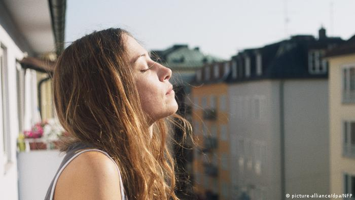 Filmstill - Alles ist gut: Eine Frau steht auf einem Balkon und hält mit geschlossenen Augen ihr Gesicht in die Sonne (picture-alliance/dpa/NFP)