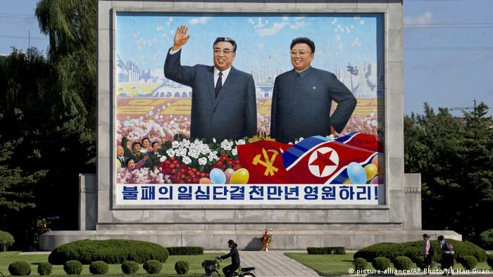 A woman cycles past a mural showing late North Korean leaders Kim Il Sung and Kim Jong Il