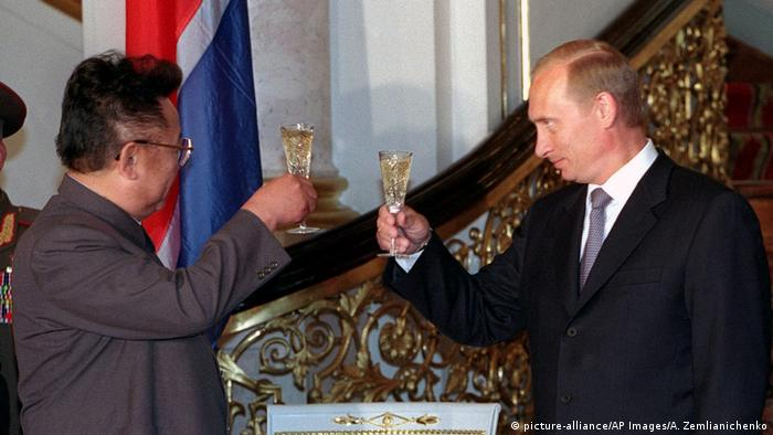Russian President Vladimir Putin (right) holds a glass to the late North Korean leader Kim Jong Il (left)