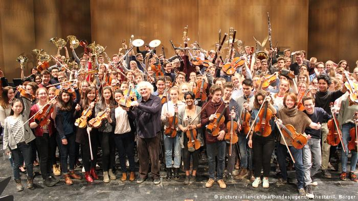 Casually clad young musicians with Simon Rattle in their midst, taking applause
