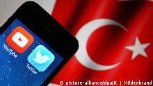 ILLUSTRATION - Ein iPhone, auf dem die Apps von Youtube und Twitter zu sehen sind, wird am 06.04.2015 in Kaufbeuren (Bayern) vor eine türkische Flagge gehalten. Foto: Karl-Josef Hildenbrand/dpa | Verwendung weltweit
