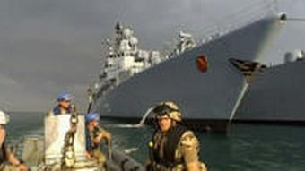Polizisten von der EU-grenzschutzagentur Frontex sitzen auf einem Boot vor einem großen Schiff (Foto: DW-TV)