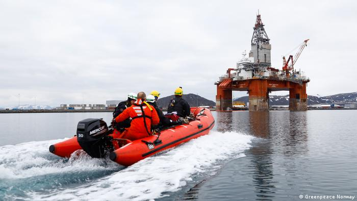 Greenpeace activists ride on an orange dingy boat to a Norwegian oil rig