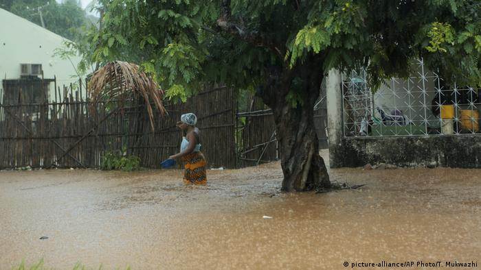 A woman wades through rising flood waters