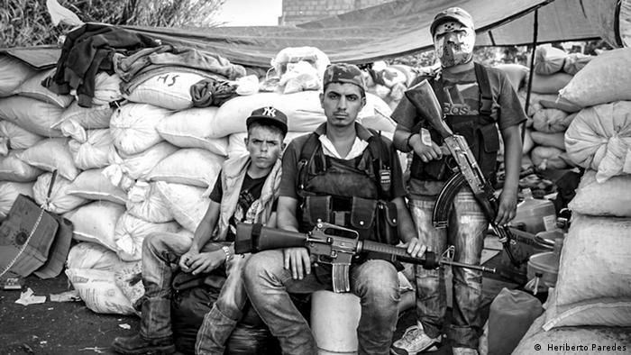 Tres menores de edad posan ante el fotoperiodista Humberto Paredes. Muestra la confusión provocada por el surgimiento de las autodefensas. Los tres menores fueron halcones de los Caballeros Templarios y sobrevivientes de una masacre que hubo en 2013 en una comunidad llamada Los Limones, en el municipio de Apatzingan.