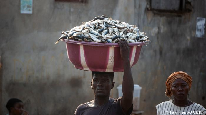 Man walks with fish on his head in a bucket