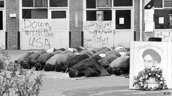 Iranian students pray inside the American Embassy compound before anti-American slogans on the third day of the occupation of the embassy in Tehran, Iran on Nov. 6, 1979. Sixty people are still held hostage against the deportation of the former Shah of Iran from the United States. In the foreground sits a portrait which apparently shows the Ayatollah Khomeini. (AP Photo)