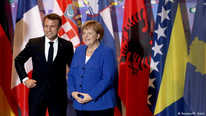 German Chancellor Angela Merkel, right, and the President of France, Emmanuel Macron, left, arrive for a group photo as part of a meeting with Balkan leaders
