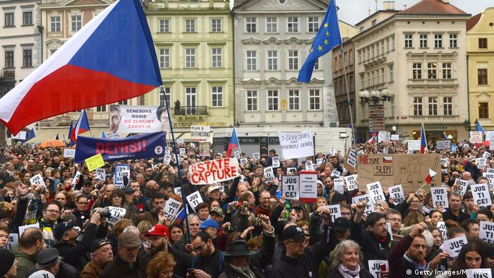 People hold up placards which read Justice as they take part in a rally demanding the resignation of Czech Prime Minister Andrej Babis