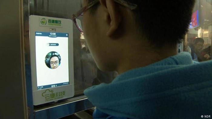 A facial recognition device scanning a student at a school in China