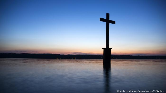 Cross in a lake at sunset (picture-alliance/imagebroker/P. Wallner)