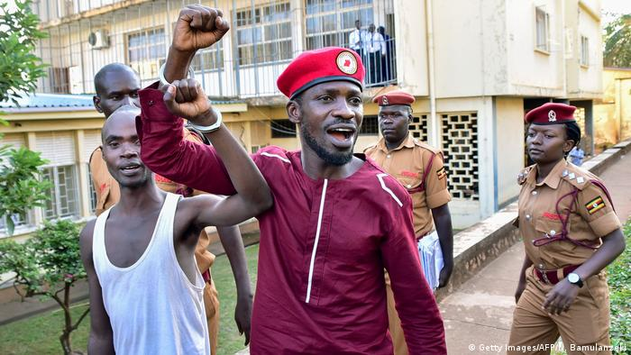 Bobi Wine, handcuffed to another prisoner, raises his arm to greet supporters