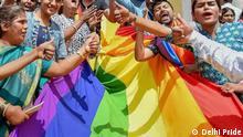 People in Delhi holding LGBTQ rainbow flag