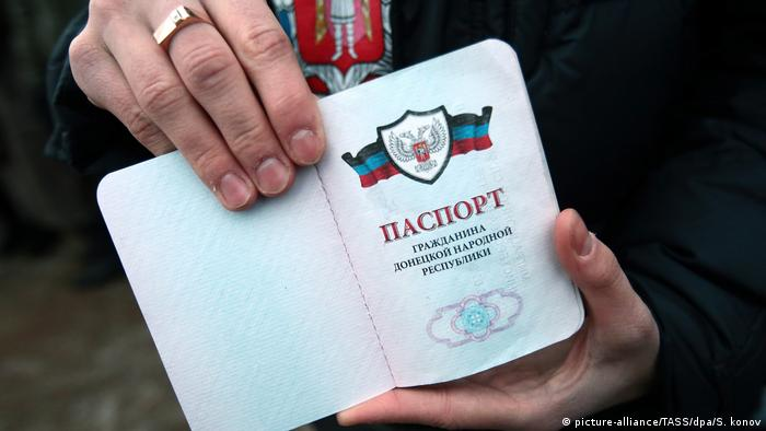 A participant in a rally in support of Donbass people shows a passport of the Donetsk People's Republic