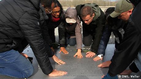 Die Temperatur der von Horst Hoheisel und Andreas Knitz gestalteten Gedenktafel zur Erinnerung an die Opfer des Konzentrationslagers Buchenwald beträgt das ganze Jahr 37 Grad. Die Teilnehmer der Reise legen ihre Hände auf die Metallplatte, in deren Mitte die Namen von über 50 Nationen der Inhaftierten eingraviert sind. Die Gruppe ist bewegt von der Wärme, die von dieser der Tafel ausgeht. (DW/L. Weller)