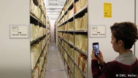 Professorin Marta Giraldos Schwerpunkt liegt im Bereich Archivforschung. Das Stasi-Archiv Berlin gilt als bekanntes Beispiel für den Umgang mit offiziellen Akten. Der Zugang leistet einen wichtigen Beitrag zur Aufarbeitung. Das Foto zeigt den Blick in einen Flur zwischen langen Aktenregalen. Eine Teilnehmerin der Delegationsreise steht im Bildvordergrund und macht mit ihrem Mobiltelefon ein Foto. (DW/L. Weller)