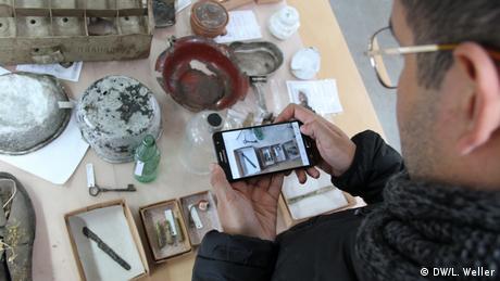 In der Restaurierungswerkstatt der Gedenkstätte Buchenwald: Ein Teilnehmer der Delegationsreise fotografiert Fundstücke aus dem Alltag des Konzentrationslagers. Das pädagogische Konzept der Gedenkstätte Buchenwald ist es, Jugendlichen durch die Mitarbeit bei der Restaurierung einen persönlichen Zugang zu dem Geschehenen zu vermitteln. (DW/L. Weller)