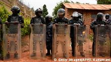 TOPSHOT - Uganda's anti-riot policemen stand guard in front of the house of Ugandan musician turned politician, Robert Kyagulanyi, commonly known by his stage name Bobi Wine (C), in Kampala, on April 23, 2019. - Ugandan police detained Bobi Wine, on April 22, 2019 a pop star turned MP who became a high-profile government critic, after shutting down one of his concerts and firing tear gas at his fans. (Photo by ISAAC KASAMANI / AFP) (Photo credit should read ISAAC KASAMANI/AFP/Getty Images)
