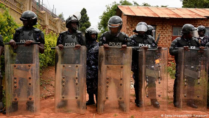 Ugandan police holding shields and wearing helmets stand in a row in front of Bobi Wine's house