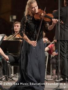 Mari Samuelsen performing with orchestral musiicans in the background (Baltic Sea Music Education Foundation e. V.)
