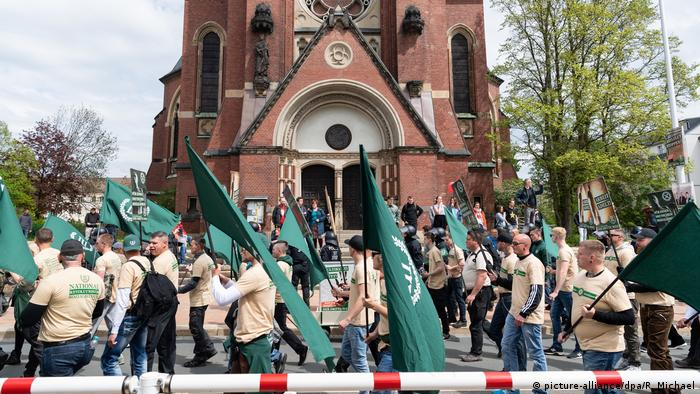 People in similar T-shirts carrying green flags in Plauen (picture-alliance/dpa/R. Michael)