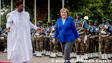 02.05.2019, Niger, Niamey: Bundeskanzlerin Angela Merkel (CDU) wird am Präsidentenpalast vom nigrischen Präsidenten Mahamadou Issoufou mit militärischen Ehren begrüsst. Niger ist die letzte Station der dreitägigen Westafrikareise der Kanzlerin. Foto: Michael Kappeler/dpa | Verwendung weltweit