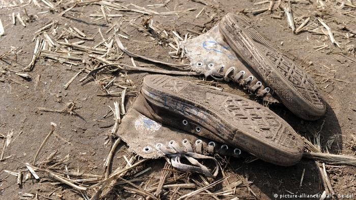 Beat-up sneakers in the mud (picture-alliance/dpa/C. Seidel)